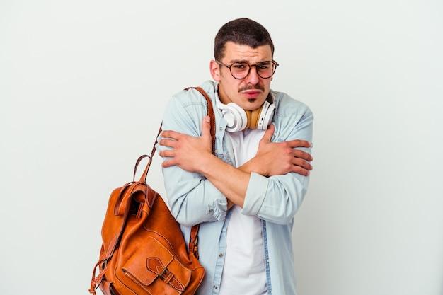 Jeune homme étudiant caucasien écoutant de la musique isolée sur fond blanc froid à cause d'une basse température ou d'une maladie.