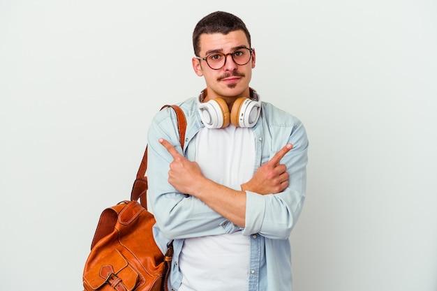 Jeune homme étudiant caucasien, écouter de la musique isolé sur fond blanc pointe sur le côté, essaie de choisir entre deux options.