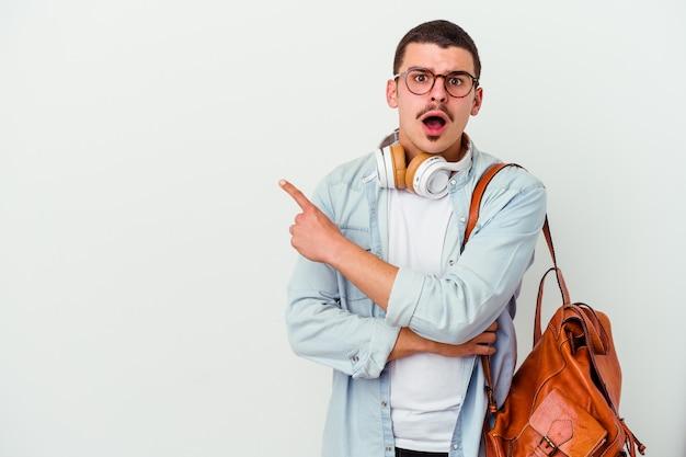 Jeune homme étudiant caucasien, écouter de la musique isolé sur un mur blanc pointant vers le côté