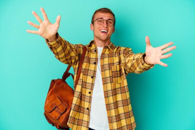 Jeune homme étudiant caucasien isolé sur un mur bleu se sent confiant en donnant un câlin à la caméra.