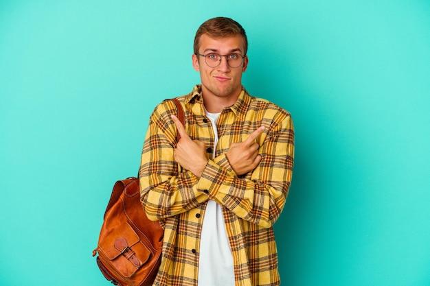 Jeune homme étudiant caucasien isolé sur des points bleus sur le côté, essaie de choisir entre deux options.