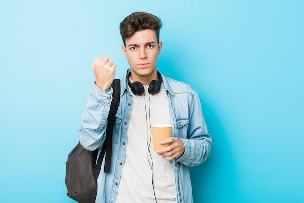 Jeune homme étudiant caucasien tenant un café à emporter montrant le poing à une expression faciale agressive.