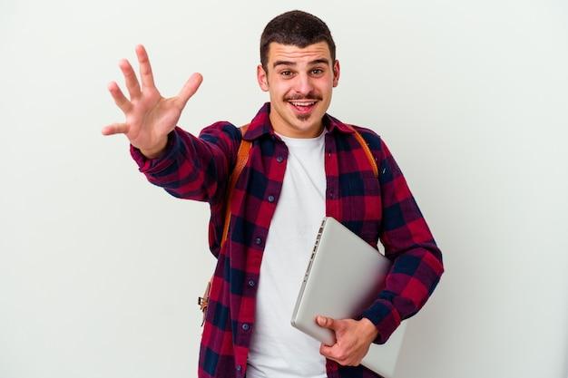 Jeune homme étudiant caucasien tenant un ordinateur portable sur blanc se sent confiant en donnant un câlin