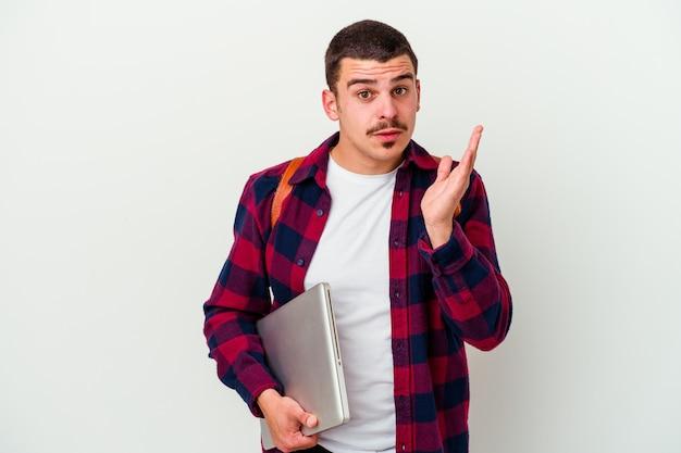 Jeune homme étudiant caucasien tenant un ordinateur portable isolé sur blanc surpris et choqué.
