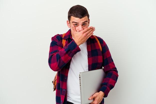Jeune homme étudiant caucasien tenant un ordinateur portable isolé sur un mur blanc choqué couvrant la bouche avec les mains