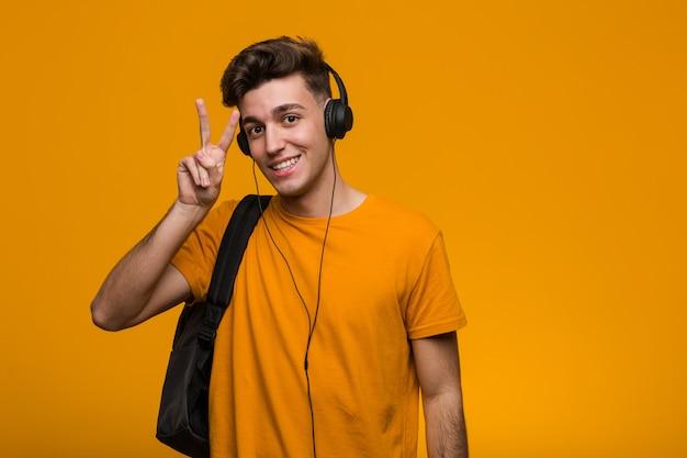 Jeune homme étudiant cool, écouter de la musique avec des écouteurs à la recherche sur le côté avec une expression douteuse et sceptique.