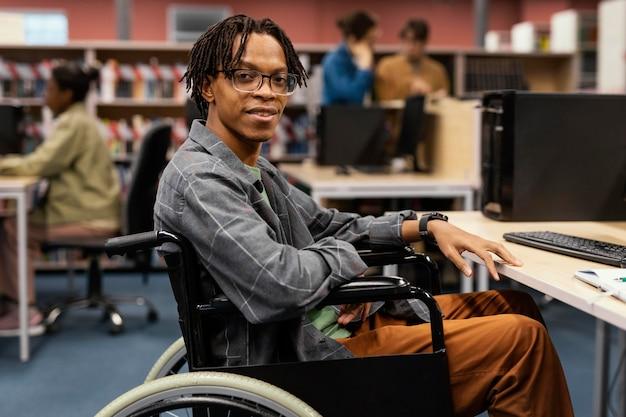Jeune homme étudiant dans la bibliothèque universitaire