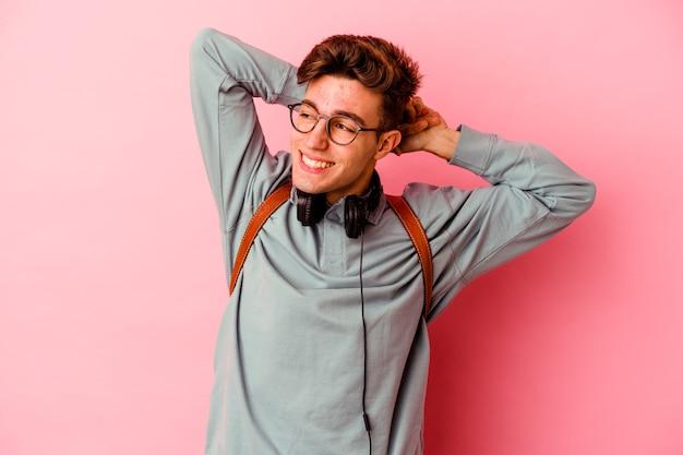Jeune homme étudiant isolé sur fond rose étirant les bras, position détendue.
