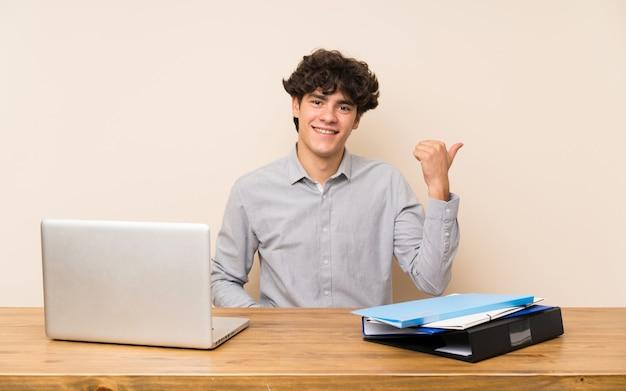 Jeune homme étudiant avec un ordinateur portable pointant sur le côté pour présenter un produit