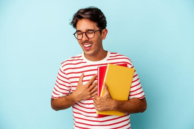 Jeune homme étudiant de race mixte tenant des livres isolés sur fond bleu en riant et en s'amusant.