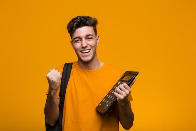 Jeune homme étudiant tenant une calculatrice célébrant une victoire ou un succès