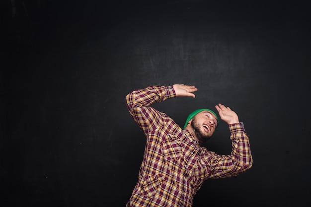 Jeune homme européen avec barbe en bonnet vert, a l'air surpris et perplexe. montrant les doigts vers le haut et le côté droit. fond noir, espace copie vierge pour le texte ou la publicité