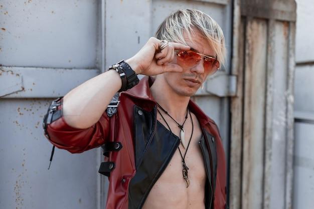Jeune homme européen blond en élégante veste en cuir noir et rouge avec des amulettes sur un cou se tient près d'un mur vintage métallique et redresse des lunettes de soleil rouges.