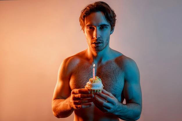 Jeune homme européen tenant un cupcake sucré avec une bougie allumée. mec musclé confiant avec torse sportif nu regardant la caméra. isolé sur fond beige avec lumière bleue. tournage en studio. espace de copie