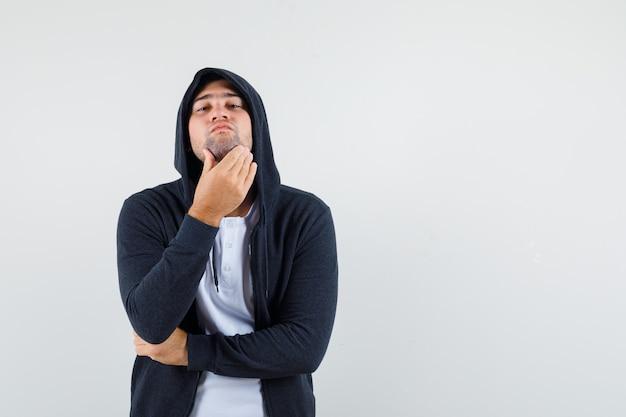 Jeune homme examinant la peau en couchant le menton en t-shirt, veste et à la recherche de beau. vue de face.