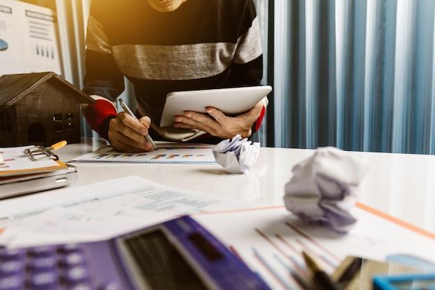 Jeune homme examine un graphique d'entreprise et tenant une tablette.