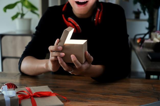 Jeune homme excité ouvrant la boîte-cadeau de noël.