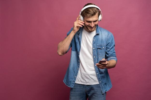 Jeune homme excité portant une chemise en jean isolé sur fond rose, écoutant de la musique avec des écouteurs et un téléphone portable