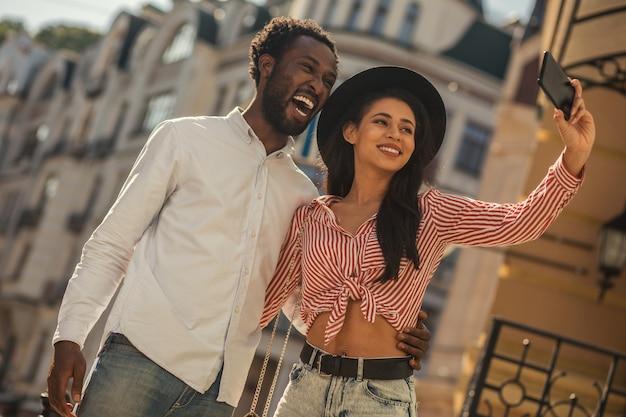 Jeune homme excité riant la bouche ouverte tandis que la jeune femme au chapeau prend un selfie avec lui