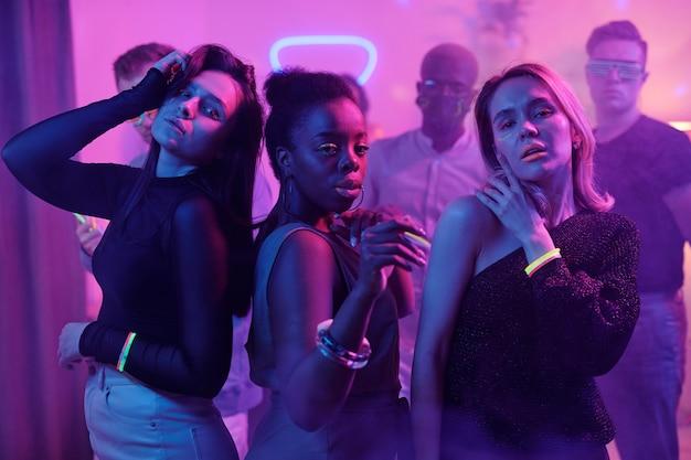 Jeune homme excité en tenue décontractée et lunettes disco et ses amis interculturels avec des bâtons lumineux dansant ensemble tout en profitant d'une fête à la maison