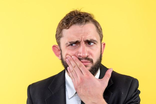 Jeune homme exécutif avec mal de dents sur jaune
