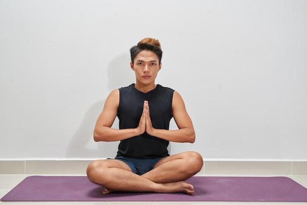 Jeune homme exerçant sur un tapis d'exercice, à l'intérieur