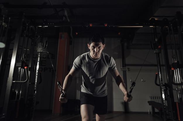 Jeune homme à l'exercice de gym sur les muscles pectoraux, la réduction des mains de crossover. tonifiant, lumière dure.
