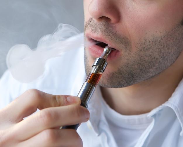 Jeune homme exhalant la fumée de la cigarette électrique