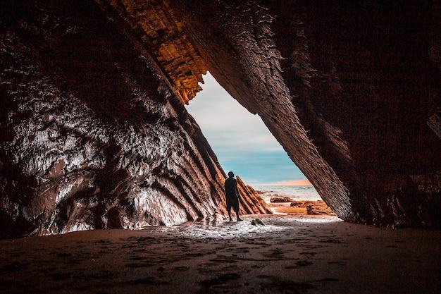 Un jeune homme explorant la magnifique grotte naturelle qui a servi au tournage de game of thrones dans le flysch de la plage d'itzurun à zumaia. pays basque...