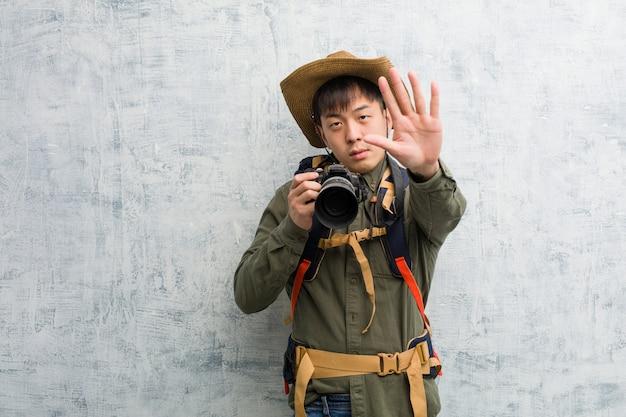 Jeune homme explorateur chinois tenant une caméra mettant la main devant
