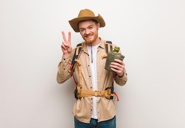 Jeune homme explorateur rousse amusant et heureux de faire un geste de victoire. il tient une cantine.