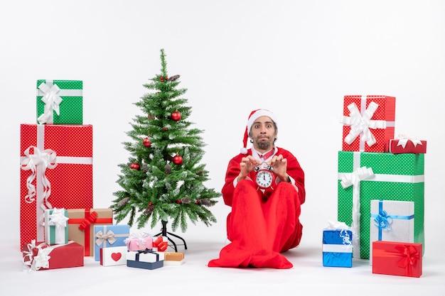 Jeune homme avec expreesion du visage insatisfait célébrer les vacances de noël assis dans le sol et montrant une horloge près de cadeaux et arbre de noël décoré
