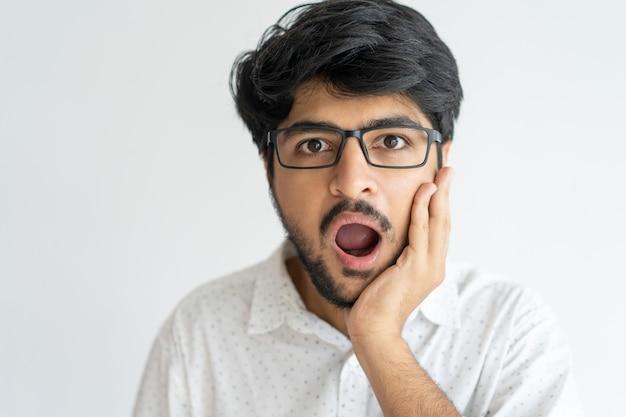 Jeune homme expressif étonné avec la bouche ouverte tenant la main sur la joue