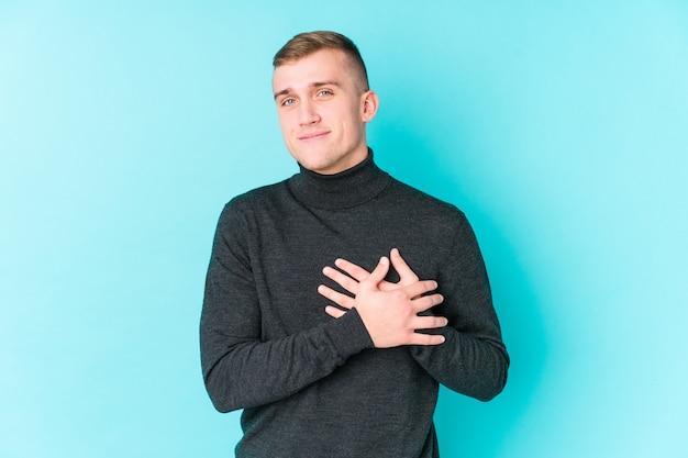 Jeune homme a une expression amicale, en appuyant la paume contre la poitrine