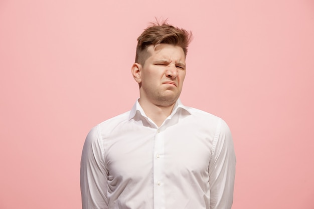 Jeune homme avec une expression dégoûtée repoussant quelque chose, isolé sur le rose
