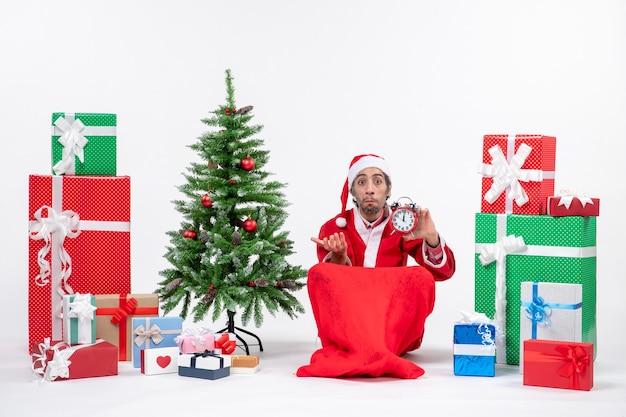 Jeune homme avec une expression faciale surprise célébrer les vacances de noël assis dans le sol et montrant une horloge près de cadeaux et arbre de noël décoré