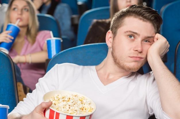 Jeune homme à extrêmement ennuyé en regardant un film au cinéma