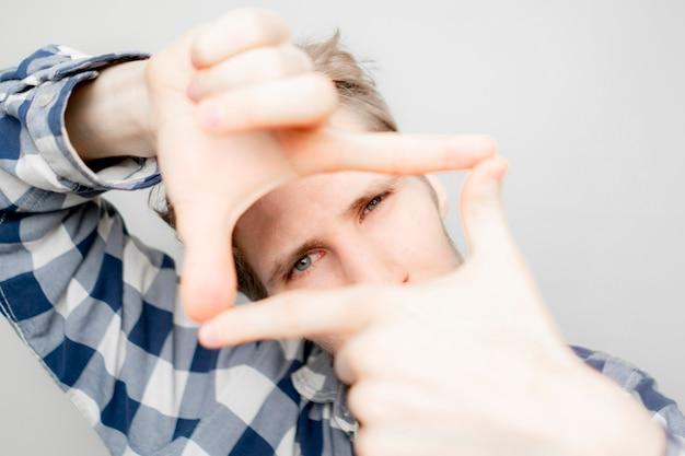 Jeune homme faire un cadre de main sur son visage sur fond clair