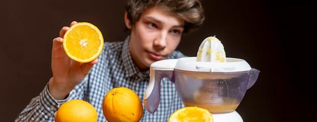 Jeune homme faire du jus avec de l'orange fraîche b