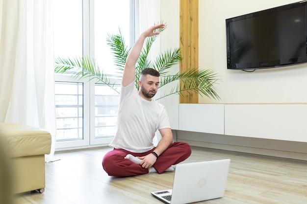 Jeune homme, faire, yoga, chez soi, à, ordinateur portable