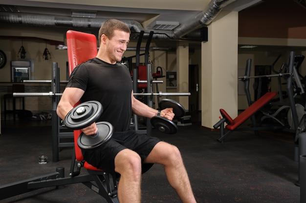 Jeune homme faisant des biceps haltère dans la salle de gym