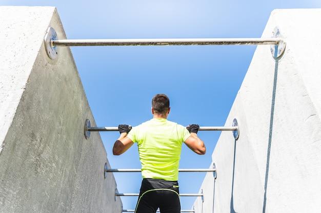 Jeune homme faisant de la callisthénie sur une barre extensible à l'extérieur.