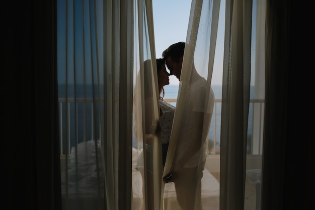 Jeune homme faisant la confession d'amour à sa charmante petite amie debout sur le balcon derrière les rideaux le matin. portrait de beau couple s'embrassant sur la terrasse après une longue journée bien remplie