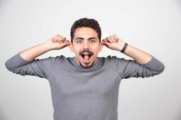 Un jeune homme faisant une drôle de tête sur un mur blanc.