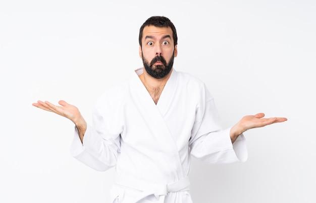 Jeune homme faisant du karaté sur blanc isolé ayant des doutes tout en levant les mains