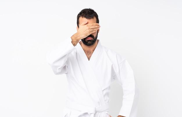 Jeune homme faisant du karaté sur blanc isolé couvrant les yeux par les mains. je ne veux pas voir quelque chose