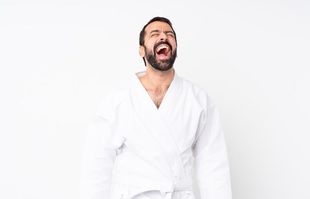 Jeune homme faisant du karaté sur des cris blancs isolés à l'avant avec la bouche grande ouverte
