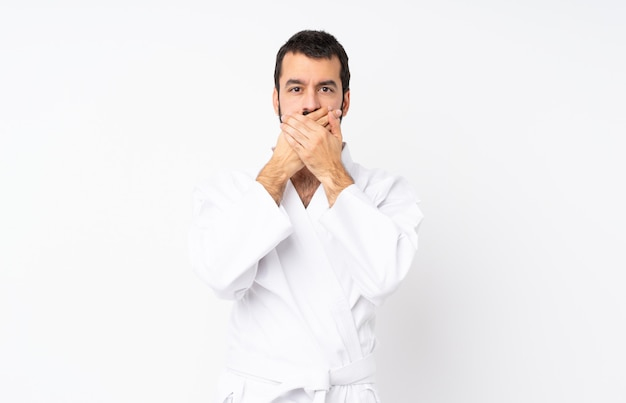 Jeune homme faisant du karaté sur fond blanc isolé couvrant la bouche avec les mains