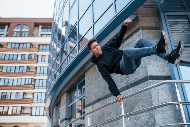 Jeune Homme Faisant Du Parkour Dans La Ville Pendant La Journée. Conception De Sports Extrêmes. Photo Premium