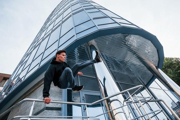 Jeune homme faisant du parkour dans la ville pendant la journée. conception de sports extrêmes.